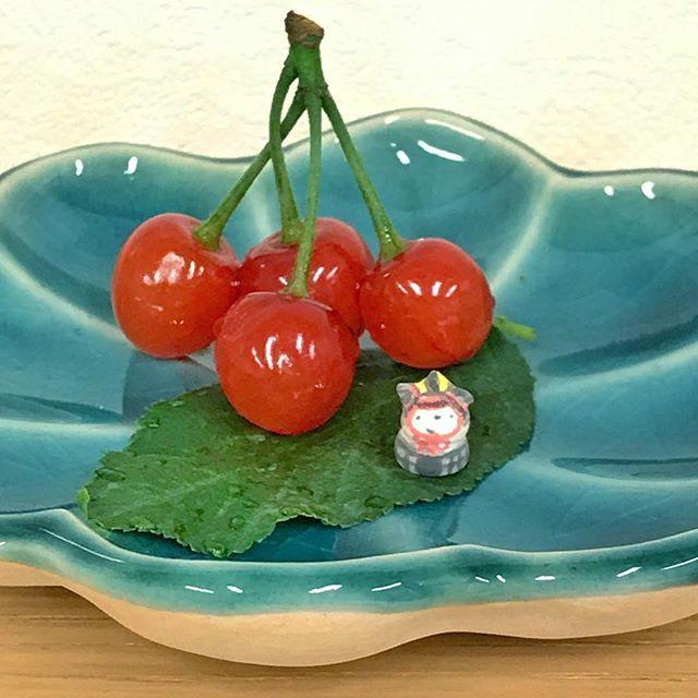 輪花豆皿の上に載せた、小さなサクランボと兜をかぶった豆つぶだるまの写真