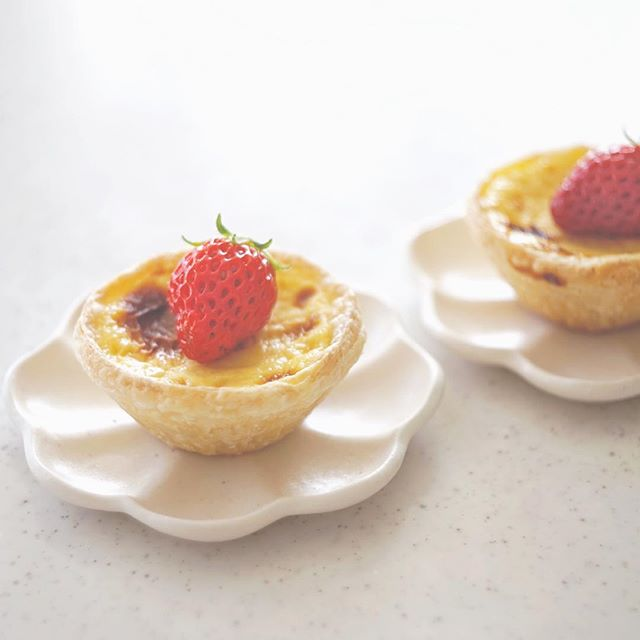 輪花豆皿に苺を添えたエッグタルトを盛り付けた写真