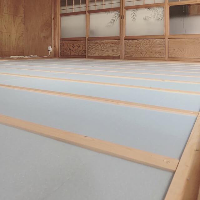 床の施工で根太材の間に断熱材を敷き詰めているところ